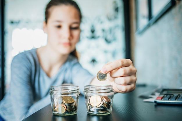 Een jong meisje stopt een munt in een pot om geld te besparen