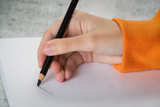 Een jong meisje trekt het album in met een zwart potlood. hand close-up.