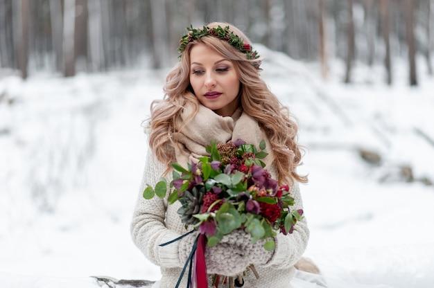 Een jong meisje van slavische uitstraling met een krans van wilde bloemen. de mooie blondebruid houdt een boeket op de winterachtergrond.