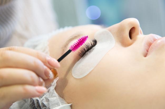 Een jong meisje verhoogt wimpers in een schoonheidssalon.