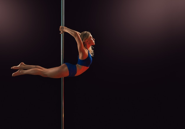 Een jong meisje voert een element op een paal uit en buigt terug in de dansstudio, in een donkere, geïsoleerde kamer.