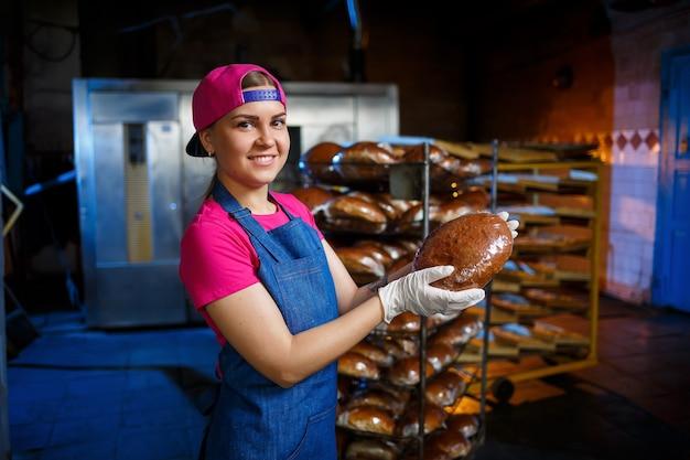Een jong meisje werkt in een bakkerij. ze zet brood op een plank. vrouwenbakker op het werk in een bakkerij. een professionele bakker houdt brood in zijn handen. broodproductieconcept