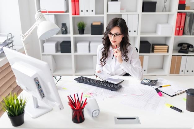 Een jong meisje werkt op de computer op kantoor en houdt een pen en een notitieboekje in haar hand.