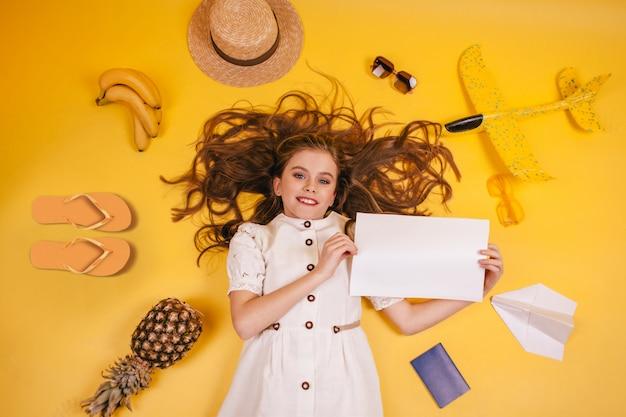 Een jong meisje wil rusten met een wit laken en andere reisaccessoires. toerist in een witte jurk kijken naar de camera