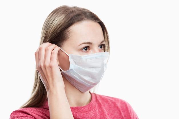 Een jong meisje zet een medisch masker op haar gezicht. voorzorgsmaatregelen en bescherming. . detailopname. ruimte voor tekst.
