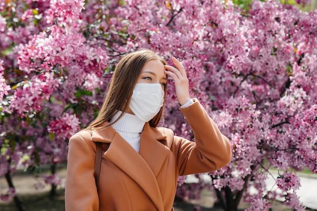 Een jong meisje zet haar masker af en ademt diep in na het einde van de pandemie op een zonnige lentedag, voor bloeiende tuinen. bescherming en preventie covid 19.