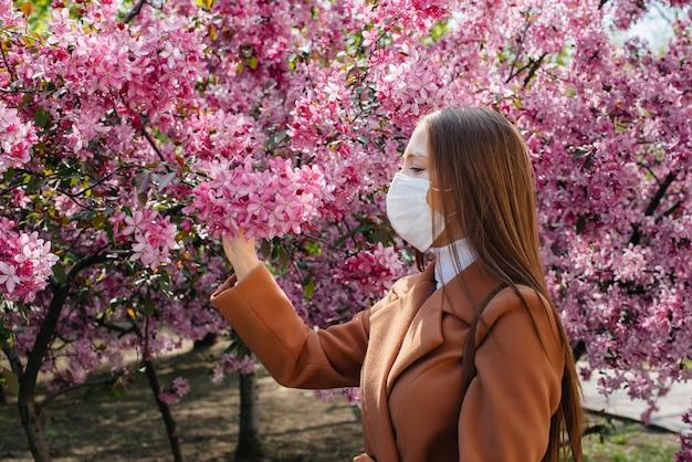 Een jong meisje zet haar masker af en ademt diep in na het einde van de pandemie op een zonnige lentedag, voor bloeiende tuinen. bescherming en preventie covid-19.