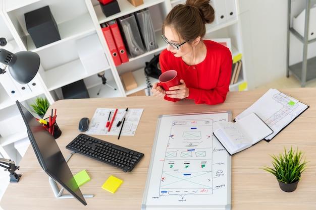 Een jong meisje zit aan de balie in het kantoor, houdt een rode beker in haar handen en kijkt naar de monitor. voor het meisje ligt een magneetbord.