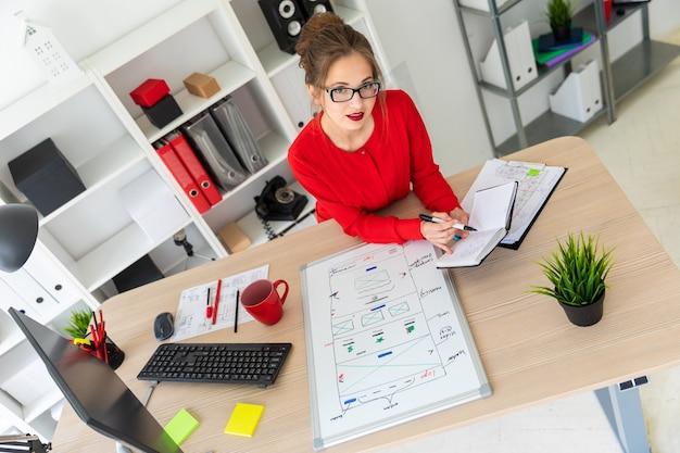 Een jong meisje zit aan de balie op kantoor, houdt een zwarte stift in haar hand en werkt met een notitieblok. voor het meisje ligt een magneetbord.