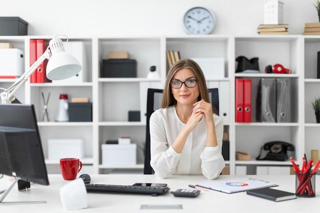 Een jong meisje zit aan de computer op het kantoor.