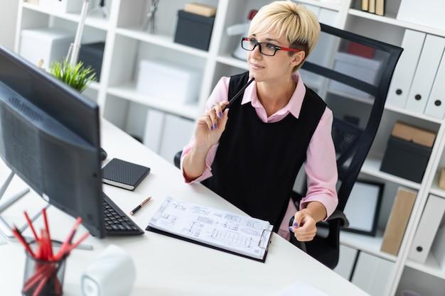 Een jong meisje zit aan een bureau op kantoor en leunde met een potlood tegen haar kin.