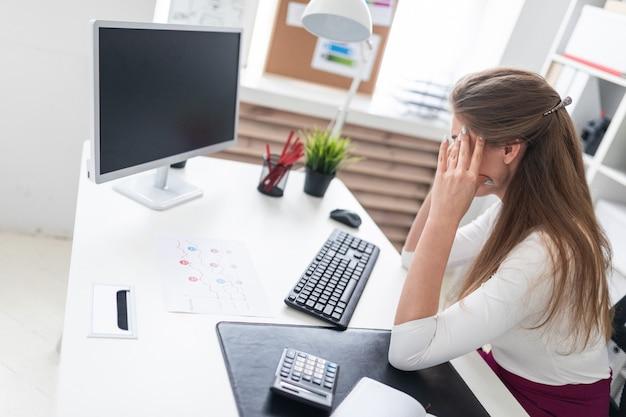 Een jong meisje zit aan een computer tafel en hand in hand op zijn hoofd.