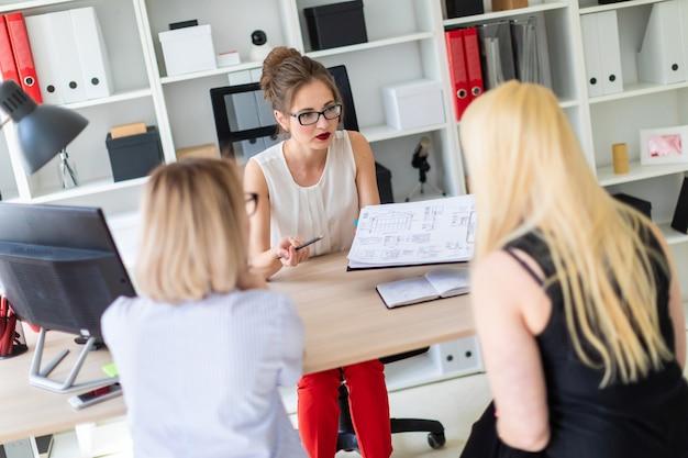 Een jong meisje zit aan een tafel in haar kantoor en praat met twee co-partners. het meisje houdt een potlood in haar hand en toont het project aan klanten.