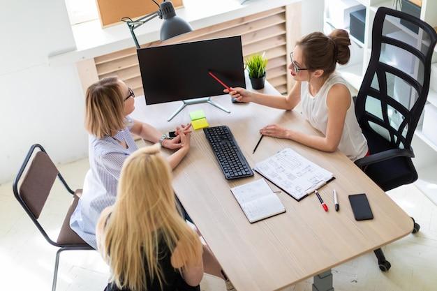 Een jong meisje zit aan een tafel in haar kantoor en praat met twee co-partners.