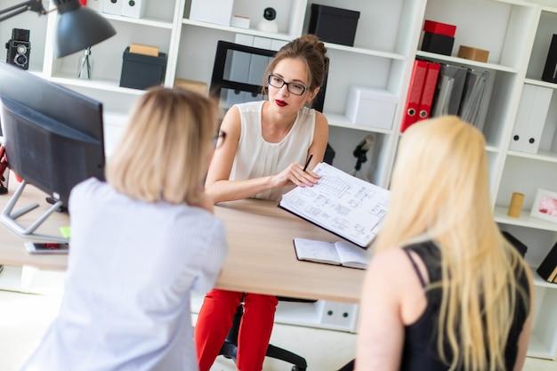 Een jong meisje zit aan een tafel in haar kantoor en praat met twee copartners.