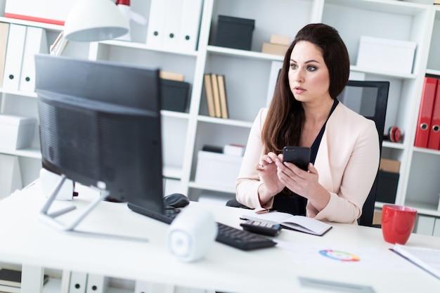 Een jong meisje zit aan een tafel in het kantoor, houdt een telefoon en kijkt naar de monitor.