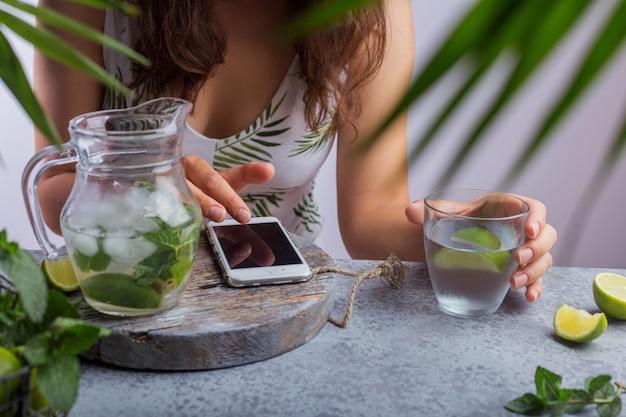 Een jong meisje zit aan een tafel met limonade in haar hand en kijkt in de telefoon
