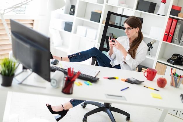 Een jong meisje zit aan een tafel op kantoor, gooit haar voet op de armleuning en kijkt in de telefoon.