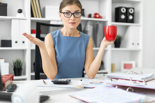 Een jong meisje zit aan een tafel op kantoor, houdt een rode kop in haar hand en werkt met documenten.