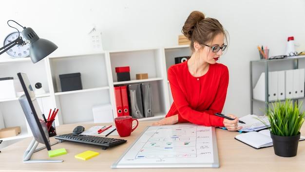 Een jong meisje zit aan het bureau in het kantoor, houdt een zwarte stift in haar hand en werkt met een notitieblok. een magnetisch bord ligt voor het meisje.