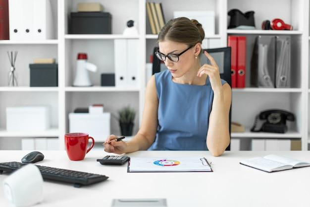 Een jong meisje zit aan het bureau op kantoor, houdt een pen in haar hand en rekent op de rekenmachine. voor het meisje ligt een laken met een diagram.
