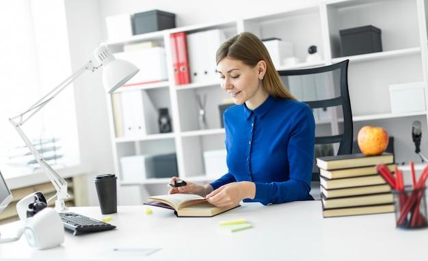 Een jong meisje zit achter een computerbureau en heeft een gele stift in haar hand. voordat het meisje een open boek ligt.