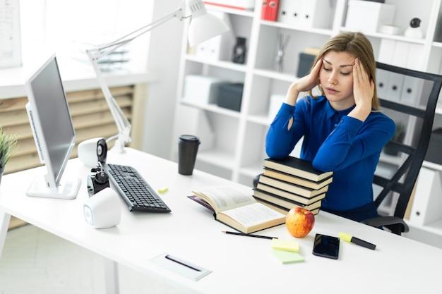 Een jong meisje zit achter een computerbureau en houdt haar handen achter haar hoofd. voordat het meisje een open boek ligt.