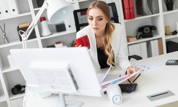 Een jong meisje zit achter het computerbureau op kantoor en houdt een beker en documenten vast.