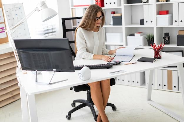 Een jong meisje zit achter het computerbureau op kantoor, houdt een potlood in haar hand en maakt aantekeningen in het document.