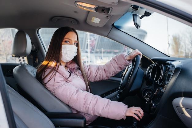 Een jong meisje zit achter het stuur in de auto in het masker tijdens de wereldwijde pandemie en het coronavirus. quarantaine.
