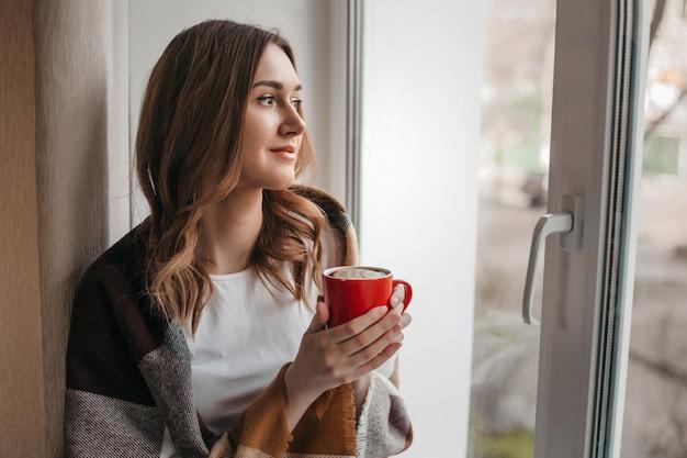 Een jong meisje zit bij het raam met een kopje hete thee en een deken, kijkt uit het raam naar de straat en glimlacht, quarantaine coronovirus, isolatie, thuis blijven