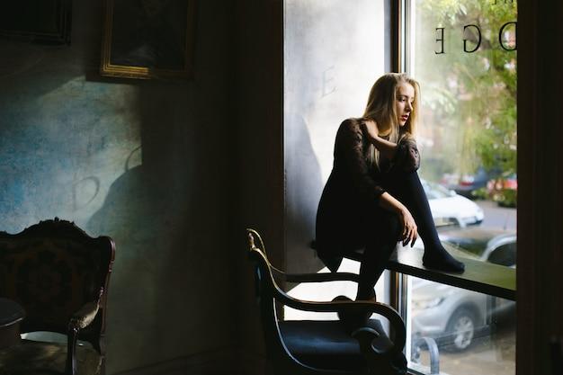 Een jong meisje zit en kijkt door een raam