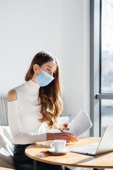 Een jong meisje zit in een café met een masker op en werkt op een computer.