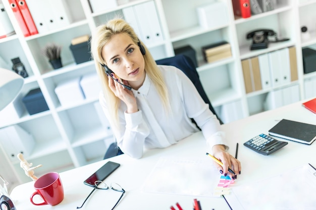 Een jong meisje zit in een koptelefoon met een microfoon op het bureau in het kantoor en maakt aantekeningen in het document.
