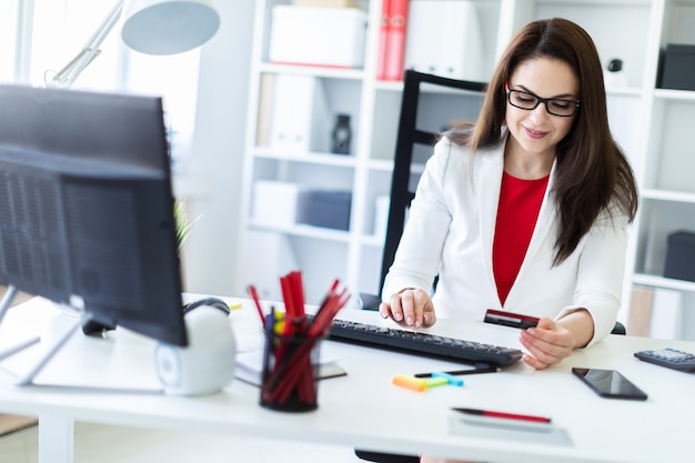 Een jong meisje zit in het kantoor aan de tafel en houdt een bankkaart.