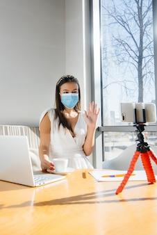 Een jong meisje zit met een masker in een café en leidt een videoblog. communicatie met de camera.