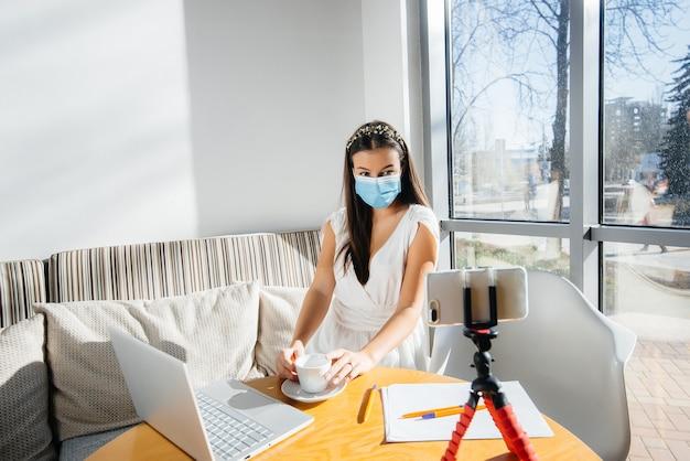 Een jong meisje zit met een masker in een café en leidt een videoblog.