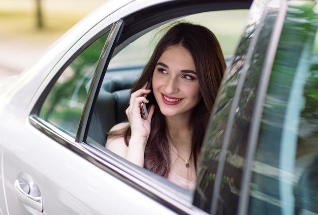 Een jong meisje zit op de achterbank van een auto en praat aan de telefoon.
