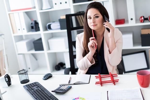 Een jong meisje zit op de oude computer, praten aan de telefoon en houdt een rood potlood.