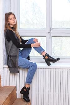 Een jong meisje zit op de vensterbank. in de studio.