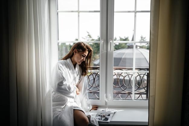 Een jong meisje zit op de vensterbank in haar badjas en leest een tijdschrift