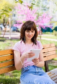 Een jong meisje zit op een bankje met een tablet in koptelefoon in het park. een schattig meisje in een roze top kijkt naar haar tablet. afstand leren.