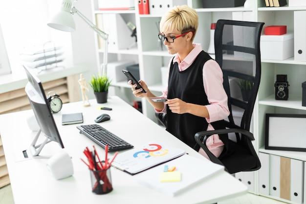 Een jong meisje zit op een computer bureau en houdt een telefoon en een bankkaart.