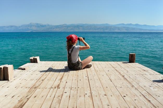 Een jong meisje zit op een houten pier en kijkt door een verrekijker.