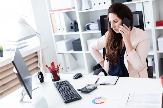 Een jong meisje zit op een oude computer, houdt een telefoon en kijkt naar de monitor.