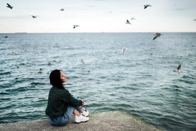 Een jong meisje zit op een pier aan zee bij winderig weer en reflecteert op het leven.