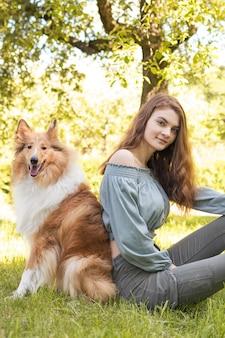 Een jong meisje zit op het gras naast haar hond