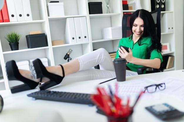 Een jong meisje zit op kantoor, gooide haar benen op tafel en houdt de telefoon in haar handen.