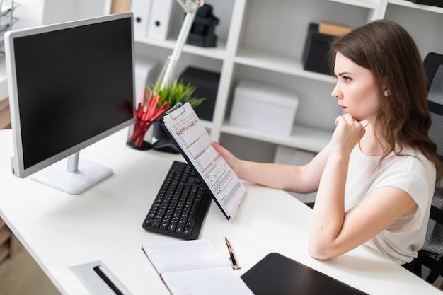 Een jong meisje zit op kantoor op de computer bureau en een bord met vellen te houden.