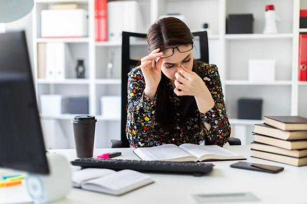 Een jong meisje zit op kantoor op de computer bureau en werkt met een boek.